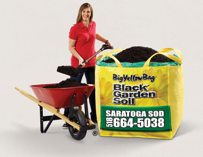 Woman next to Big Yellow Bag Garden Soil